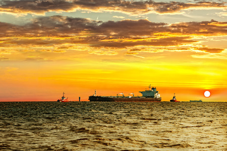 escorting: Tanker with escorting tugs at sea at sunset. Stock Photo