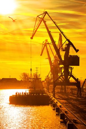 transporte: Silhuetas de guindastes e embarcações no porto de Gdansk, na Polônia.