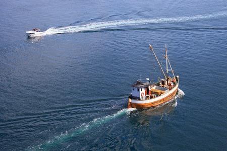 trawler: Old wooden fishing boat trawler on sea. Stock Photo