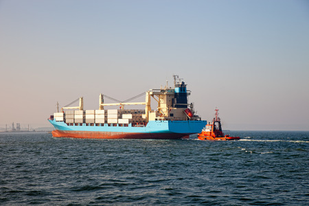 assisted: Container ship arriving at port, assisted by tugboat. Stock Photo