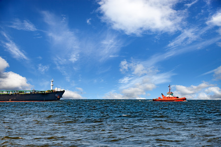 towing: Tug boat towing ship on sea.