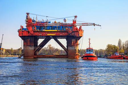 marine industry: Oil rig in the company of a tug boats enters a port. Stock Photo