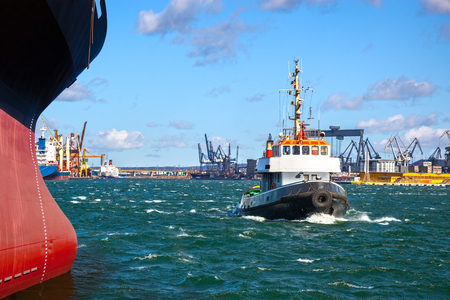 cargo vessel: A cargo ship with the assistance of a tugboat in port. Stock Photo
