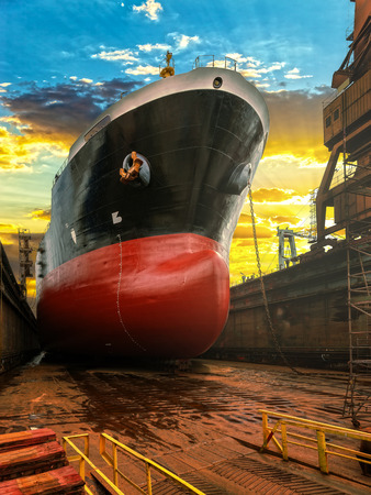 Big ship during repairs on dry dock in shipyard.