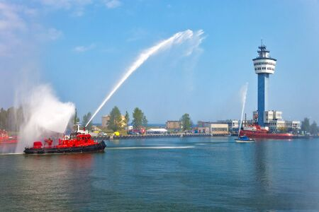 water spray: Fire fighting boat sprays water in port.