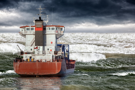 Cargo ship during storm in ocean. Stock Photo