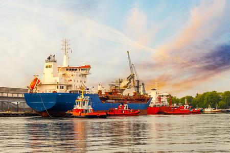maneuver: Tugboats maneuver a cargo ship in port of Gdansk, Poland.