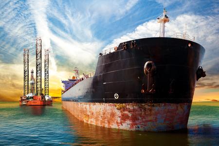 Tankschiff und Ölplattform auf Offshore-Bereich bei Sonnenuntergang. Standard-Bild