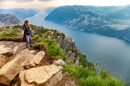 trekking pole: Girl hiker with trekking pole and looking on Lysefjorden, on July 12, 2015 in Forsand, Norway. Editorial