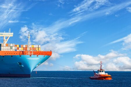Tugboat towing a large container ship on sea. Stock Photo