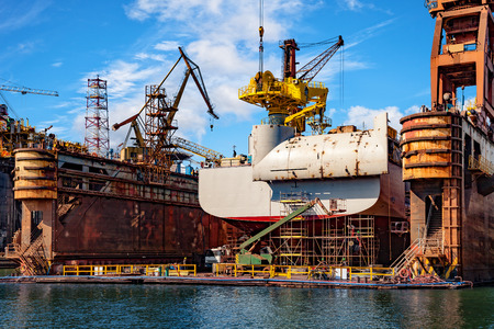 Big ship under repairing on floating dry dock in shipyard.