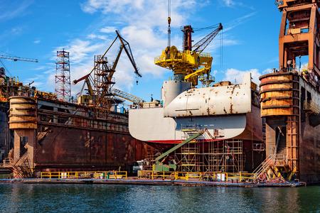 Groot schip in het kader van het herstellen op drijvende droogdok in scheepswerf.