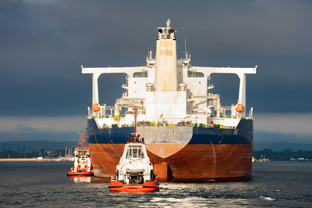 cargo vessel: Tugboats towing a large tanker ship in port. Stock Photo