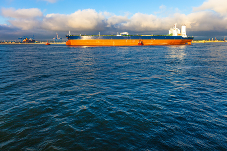 escorting: Tugboats pulling the tanker at sea in the morning. Stock Photo