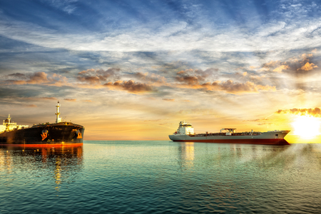 Two tanker ships on sea in the rays of the setting sun. Stock Photo