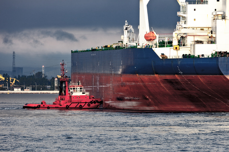 Tugboat pushes a large tanker ship in port.