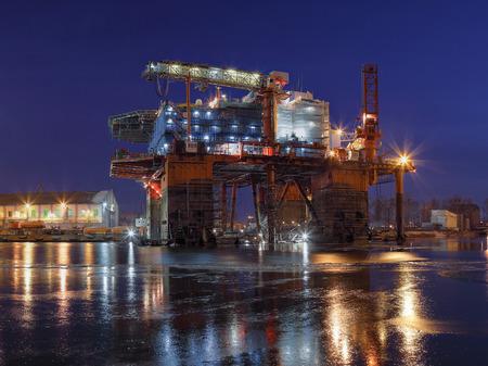 shipbuilding: Oil rig under construction at night in Gdansk, Poland.