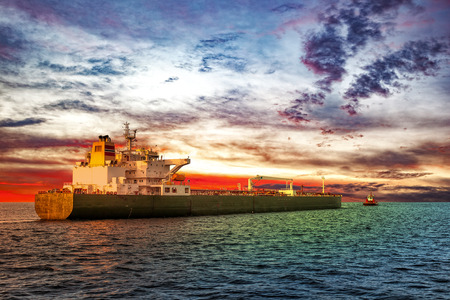 escorting: Tanker ship with escorting tugboat on sea at sunrise. Stock Photo