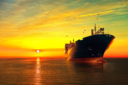 Oil tanker ship at sea on a background of sunset sky. Stock Photo