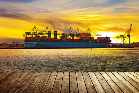 View from wooden pier with container ship in port during sunset.