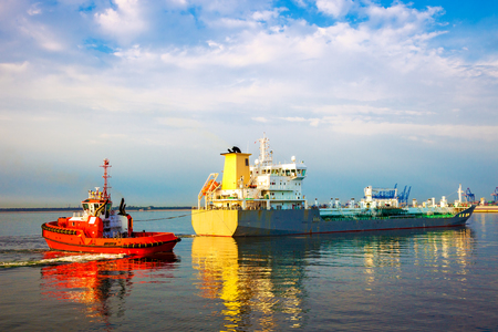 Tugboat towing tanker ship in port. Stock Photo