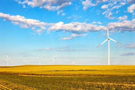 Alternative energy wind turbines on green field. Stock Photo