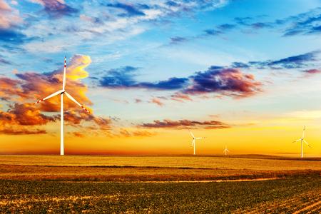 sun energy: Wind turbine farm at sunset time. Stock Photo