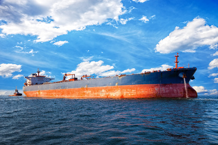 unloading: Tug boat towing a tanker ship at sea.