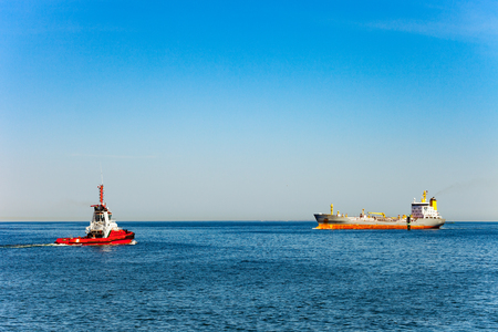 Red tug boat approaching to assist tanker. Reklamní fotografie