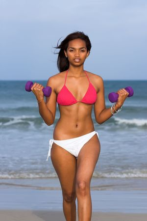 Ethnic Fitness model in bikini with dumbbells in her hands photo