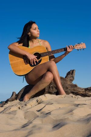 Girl sitting on a log playing a guitar at the beach