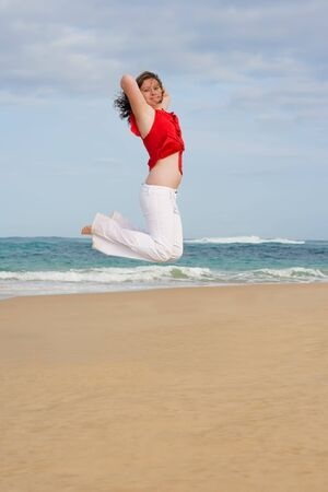 Jumping for joy on the beach wearing red and white photo