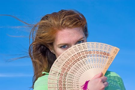 sexiness: Attractive red head using an Asian fan
