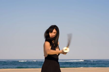 rapier: attractive model swinging a sword at the beach
