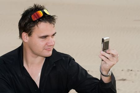 Handsome male model taking a photo of himself with a cellphone camera on the beach Stock Photo - 2147239