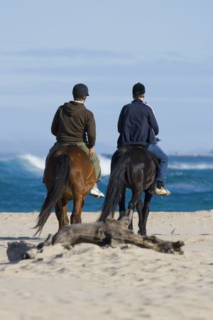 A Pair of Horse Riders taking their steeds out to the beach