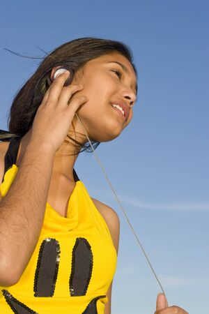 Girl listening to music through headphones photo