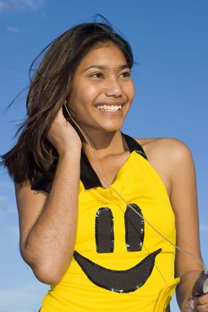 exuberant: Girl with smiley face top listening to music on headphones