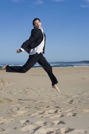 Young professional jumping wearing a business suit photo