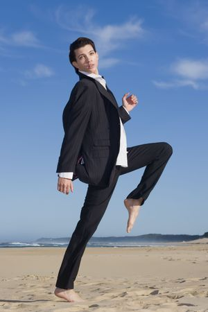 Young business man in suit on the beach photo