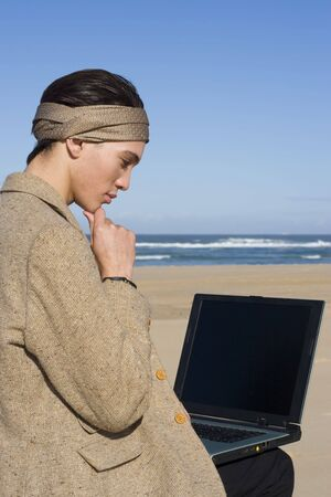Professional working on his laptop at the beach photo