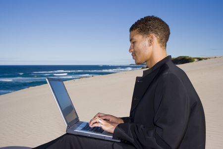 Young professional working on a laptop at the beach photo