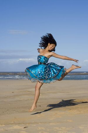 exuberant: Pretty girl jumping wearing a puffy blue dress Stock Photo