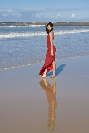 Beautiful girl in red dress on the beach photo