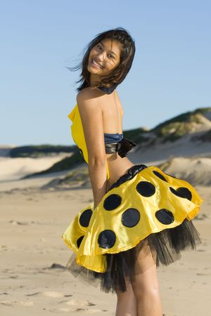 poised: Playful girl wearing a yellow polka dot outfit