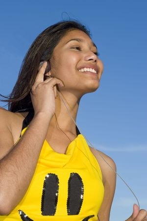 Girl with smiley face top listening to music on headphones photo