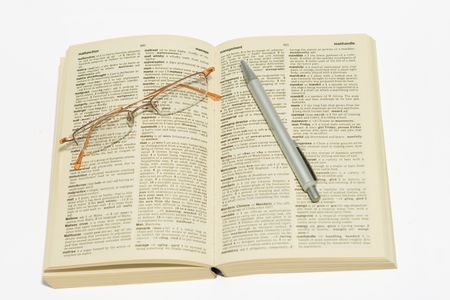 Reading glasses and pen on dictionary, pen pointing at management Zdjęcie Seryjne