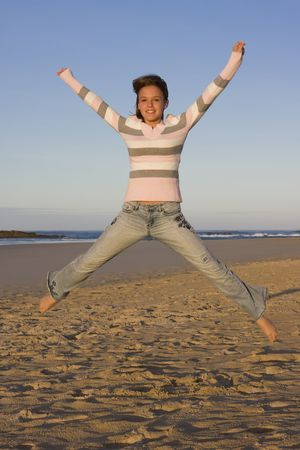 poise: Young girl jumping into the air, with arms outstretched