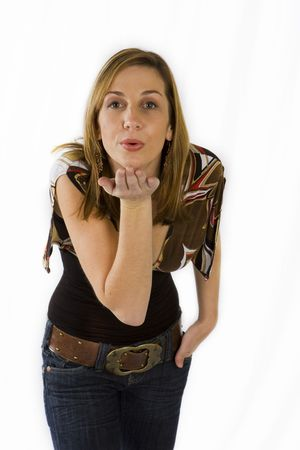 Beautiful young woman blowing kisses against white background photo