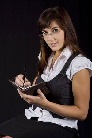Sophisticated business lady with diary, looking over the rim of her glasses photo
